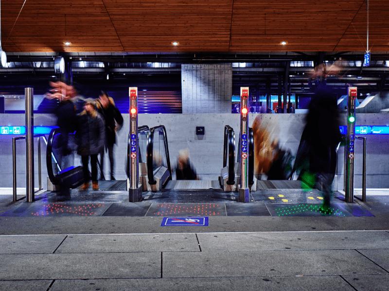 luminous escalator arrow display in train station made of fiber optic cables